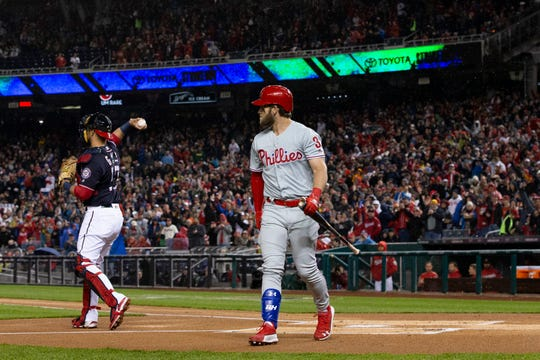 Phillies' Bryce Harper walks to the dugout after striking out during the first inning of a game against the Nationals Tuesday in Washington.