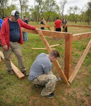 Joe Rock, left, supervises a crew of airmen volunteers as they build the framework for a cargo net crawl on the T.H.O.R course in Lucy Park Wednesday.