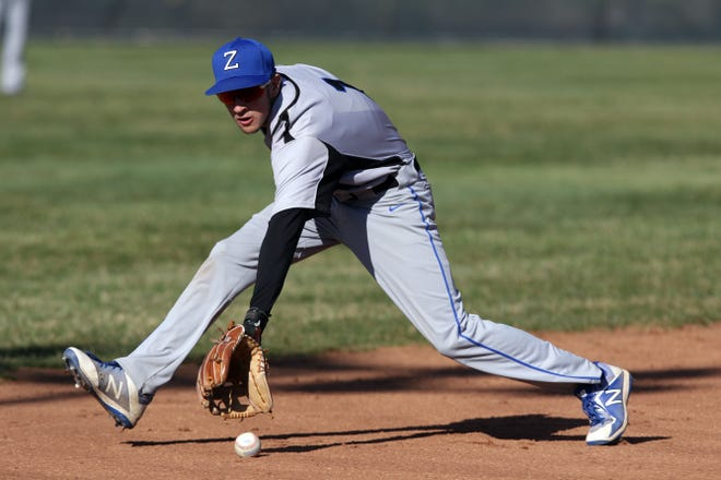 Zanesville shortstop Avery Parmer ranges to his right for a grounder against Coshocton in Coshocton's Lake Park on Wednesday.