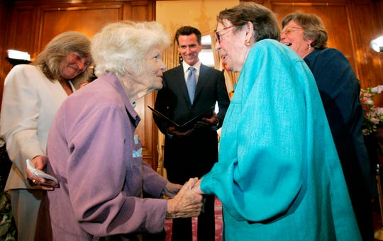 In this 2008 photo, Del Martin, 87, center left, and Phyllis Lyon, 84, center right, are shown being married by San Francisco Mayor Gavin Newsom , center, in a special ceremony at City Hall in San Francisco. Lyon and Martin became the first officially married same sex couple after California's Supreme Court declared gay marriage legal.