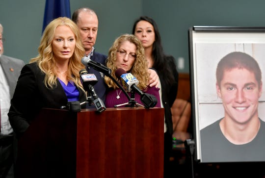 In this May 5, 2017 file photo, Jim and Evelyn Piazza stand by as Centre County District Attorney Stacy Parks Miller, left, announces the results of an investigation into the death of their son Timothy Piazza, seen in photo at right, a Penn State University fraternity pledge, during a press conference in Bellefonte, Pa.