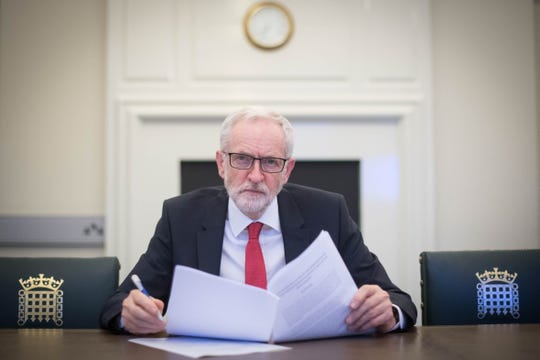 """Britain's main opposition Labour Party leader Jeremy Corbyn poses with a copy of the Political Declaration setting out the framework for the future UK-EU relationship, in his office in the Houses of Parliament in London on April 2, 2019. Prime Minister Theresa May said Tuesday she would ask the EU to delay Brexit again to avoid Britain crashing out of the bloc next week, signalling she could accept a closer relationship with Europe to break months of political deadlock. In a move which enraged the Brexit-supporting wing of her Conservative Party, she also offered to work with Labour main opposition leader Jeremy Corbyn, who favors closer ties with the European Union. Corbyn responded saying he was """"very happy"""" to meet."""