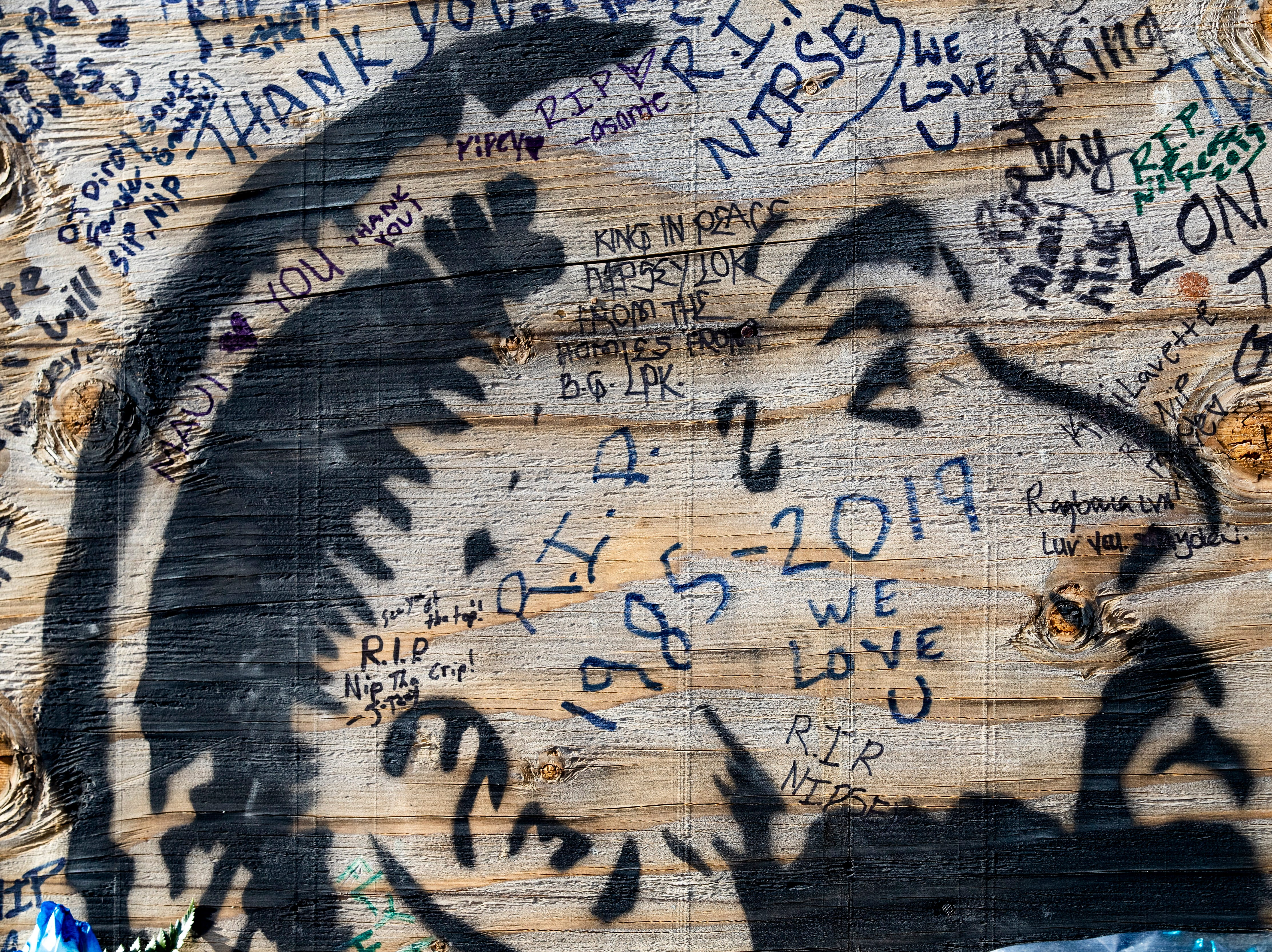 A portrait of rapper Nipsey Hussle is drawn on planks of wood near his shop where where he was shot in Los Angeles, Calif. on April 2, 2019.
