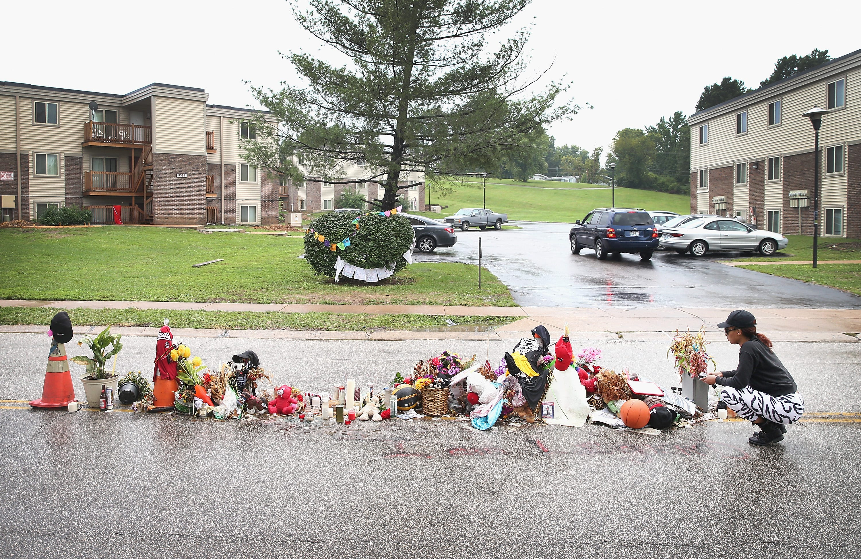 Tamika Staton leaves a message at a memorial in the middle of the road where teenager Michael Brown died after being shot by a police officer in 2014 in Ferguson, Mo., an incident that sparked investigations, protests and a nationwide discussion about policing.