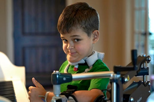 Braden Scott gives a thumbs up as he pauses while practicing on the piano in Tomball, Texas on Friday, March 29, 2019. Braden was diagnosed with the mysterious syndrome called acute flaccid myelitis, or AFM, in 2016 and was paralyzed almost completely. But since then he has recovered much of his muscle function.