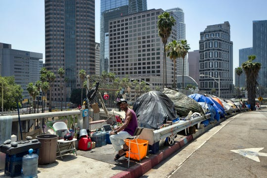 A homeless man sits at his tent along the Interstate One hundred ten small-secure valid of entry to toll road in downtown Los Angeles. California Gov. Gavin Newsom met with the mayors of some of California's largest cities to discuss the homeless grief closing month.