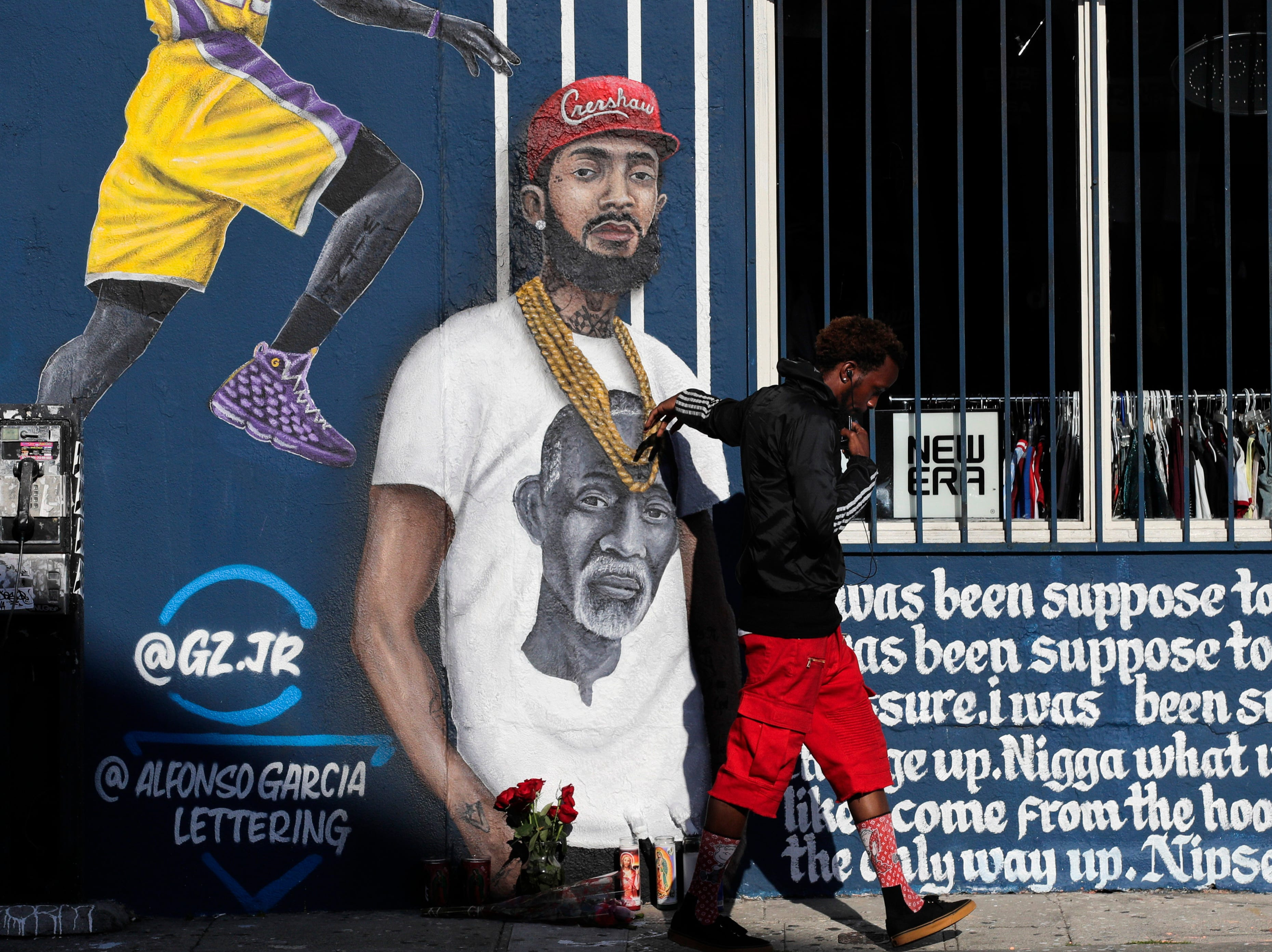 A man touches a mural depicting slain rapper Nipsey Hussle, Tuesday, April 2, 2019, in Los Angeles.