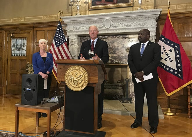 In this Sept. 12, 2018, file photo, Arkansas Gov. Asa Hutchinson, center, talks at a news conference at the State Capitol in Little Rock about the state's work requirement for its expanded Medicaid program. The Arkansas House voted Tuesday to keep the state's Medicaid expansion for another year, breaking a deadlock that left the program's future uncertain.