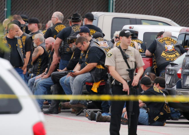 AMcLennan County deputy stands guard near a group of bikers in the parking lot of a Twin Peaks restaurant in Waco, Texas, on May 17, 2015.