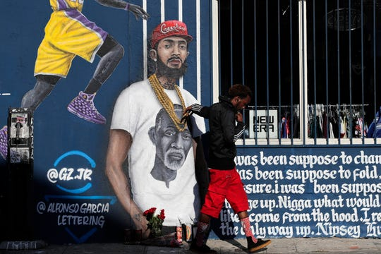 A man touches a Los Angeles mural depicting slain rapper Nipsey Hussle, who was shot and killed arch 31, outside of his clothing store.