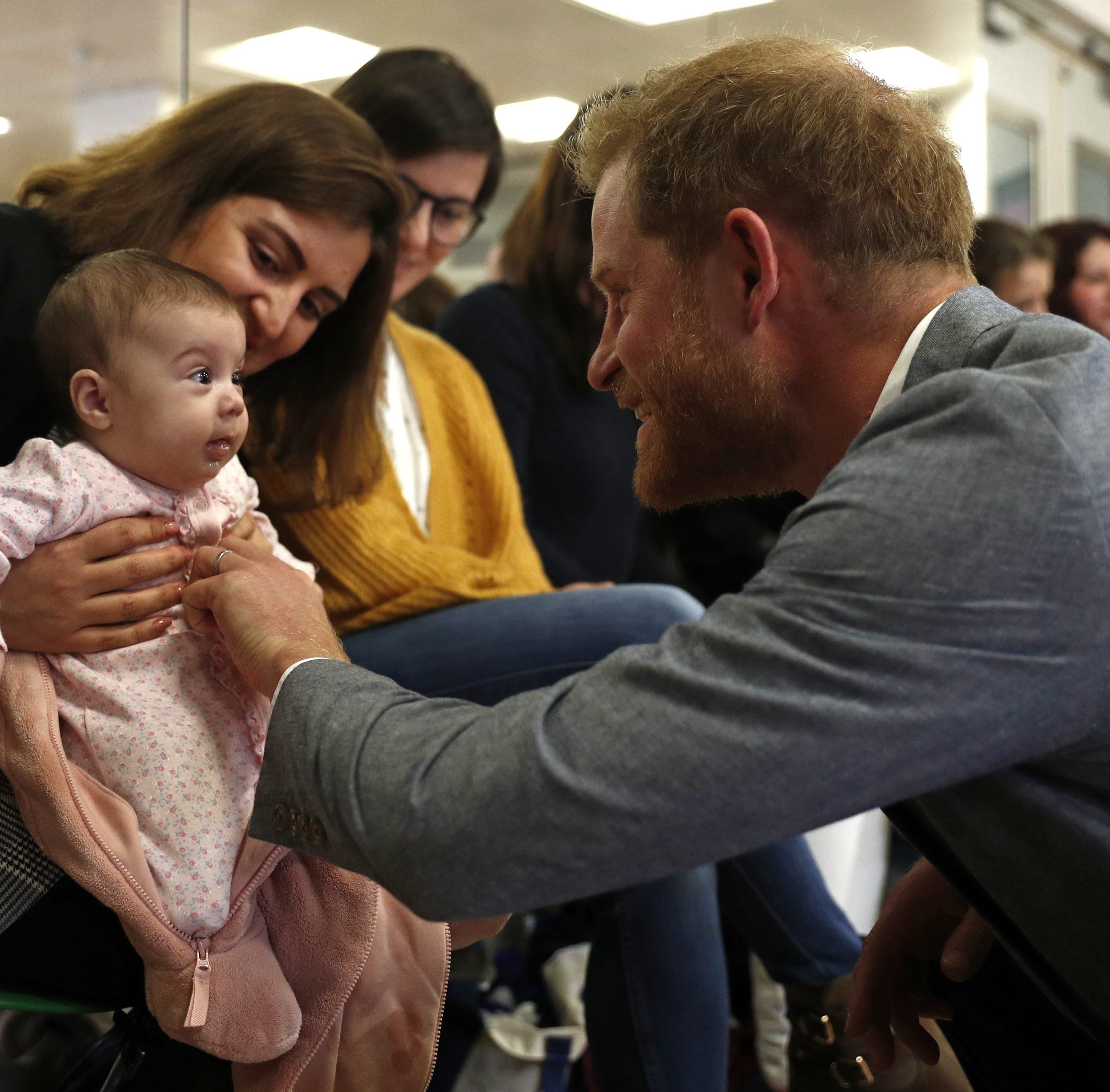 Prince Harry chats with 3 months old baby Naz and mother Maria Ahmad as they watch a ballet class for 4 to 6 year olds, during a visit to YMCA South Ealing on April 3, 2019 in London.