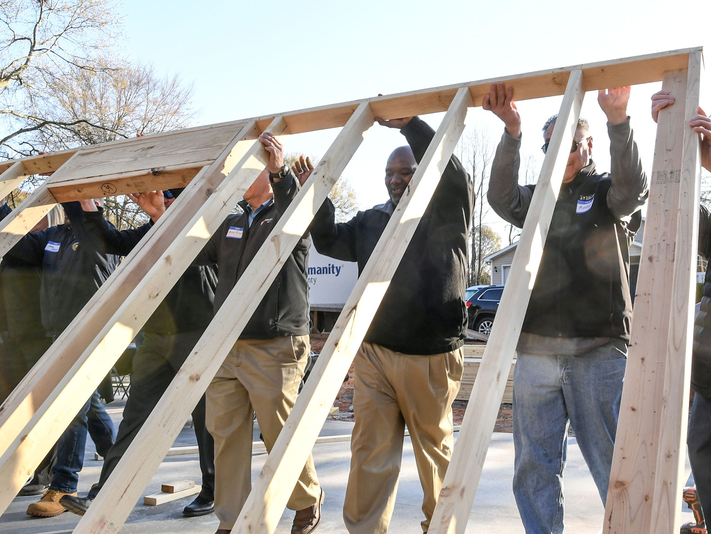 Volunteers Michael Cunningham, middle, Vice President of Community Health Partnerships for AnMed Health, and Rusty Burns, right, Anderson County administrator help raise a wall at a Habitat for Humanity of Anderson County home build for new homeowner recipient Victoria Santos in Anderson Thursday. The home is the eighth on Melrose Place in Anderson since Clemson football players, including Deshaun Watson, helped built the first in the fall of 2015.