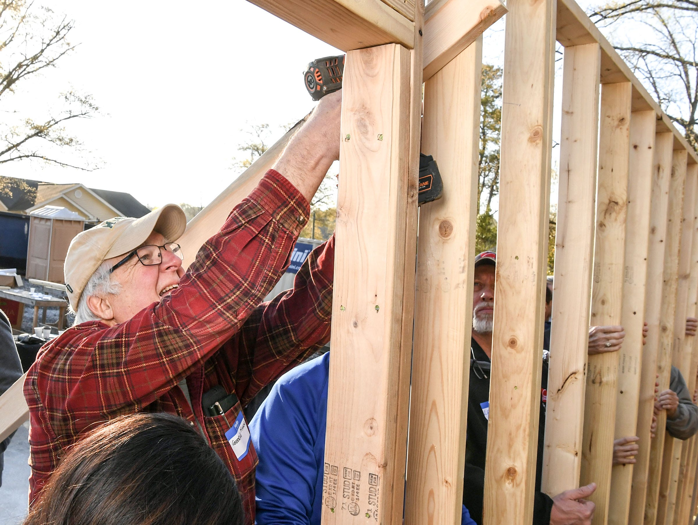 George Mason, retired board of directors and volunteer for Habitat for Humanity of Anderson County, helps raise a wall at a home build for new homeowner recipient Victoria Santos in Anderson Thursday. The home is the eighth on Melrose Place in Anderson since Clemson football players, including Deshaun Watson, helped built the first in the fall of 2015.