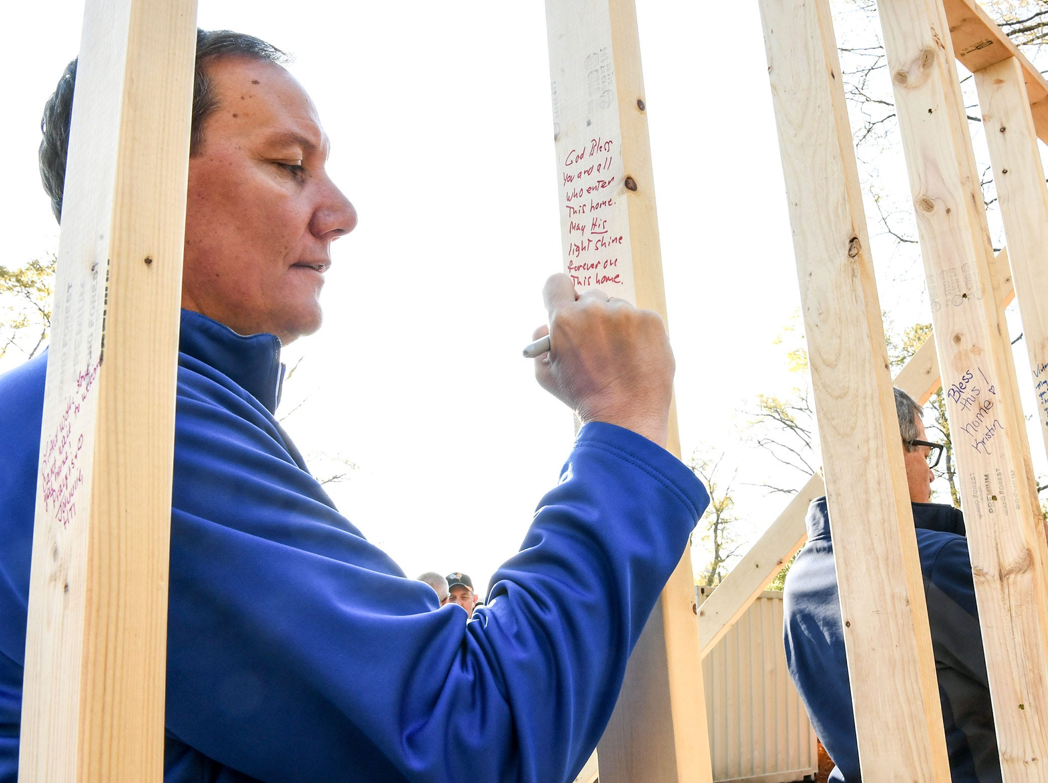 Randy Bunch of Bosch writes a well-wishing notes on a wood wall after helping raise it at the Habitat for Humanity of Anderson County home build for new homeowner recipient Victoria Santos in Anderson Thursday.