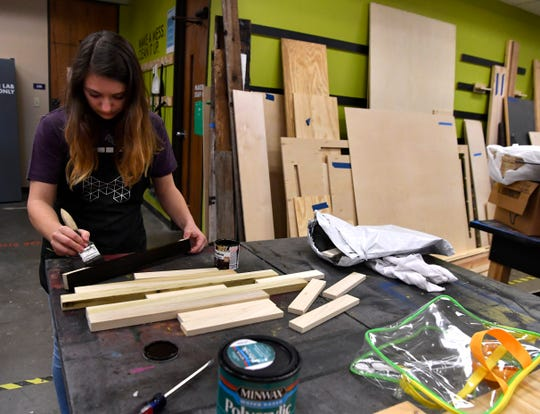 Laurel Drain stains the wood frames of the inspirational signs she was creating March 29 in the Maker Lab at Abilene Christian University.
