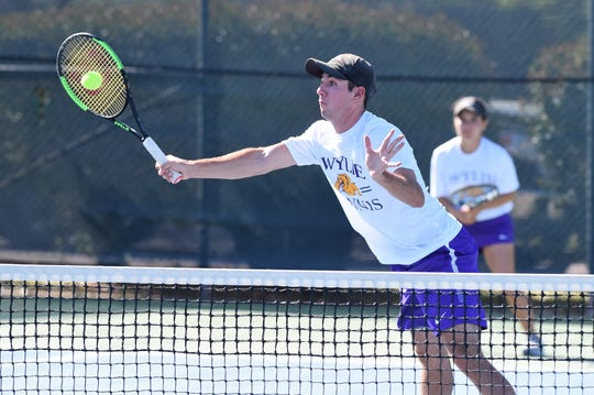Wylie's Lane Adkins hits a shot at the net during the District 4-5A mixed doubles final at Rose Park on Thursday. Adkins and partner Analeah Elias won the title in three sets.