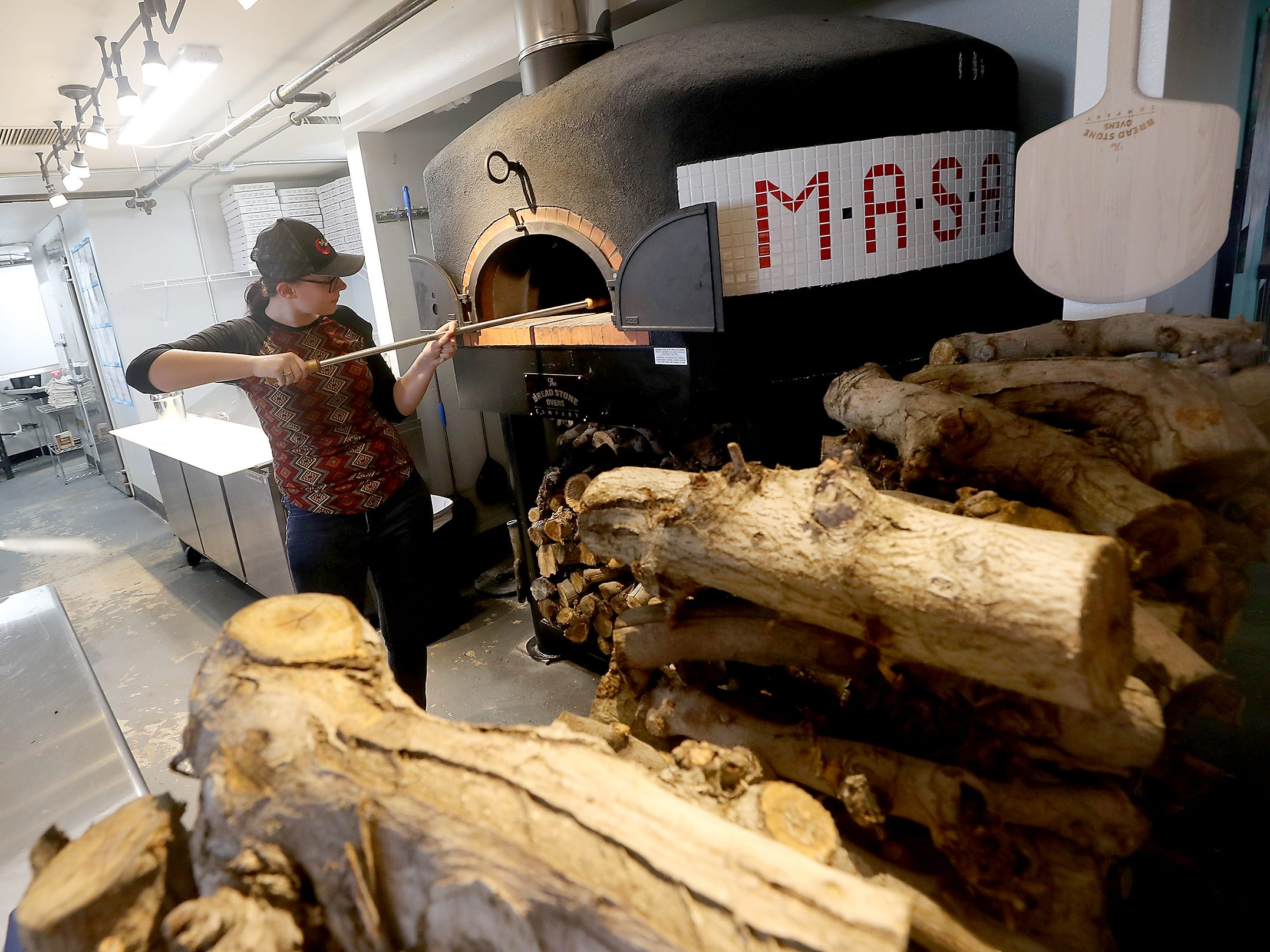 Conner Rains stokes the wood-fired pizza oven at M*A*S*A Pizza in Port Orchard on Thursday, April 4, 2019.