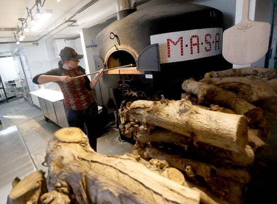 Conner Rains stokes the wood-fired pizza oven at M*A*S*A Pizza in Port Orchard. The business, started by a Navy nurse who loved making pizza in 2017, now has a brick-and-mortar location after starting as a mobile business.