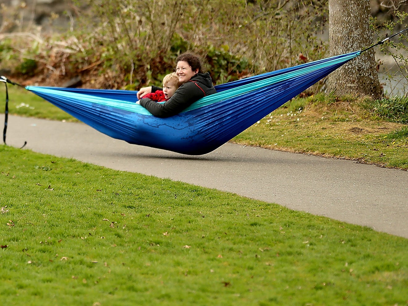 Rochelle Graham holds son Arthur, 2, in a hammock as daughter Hazel wanders over after playing in the grass at Evergreen Rotary Park in Bremerton on Wednesday, April 3, 2019.