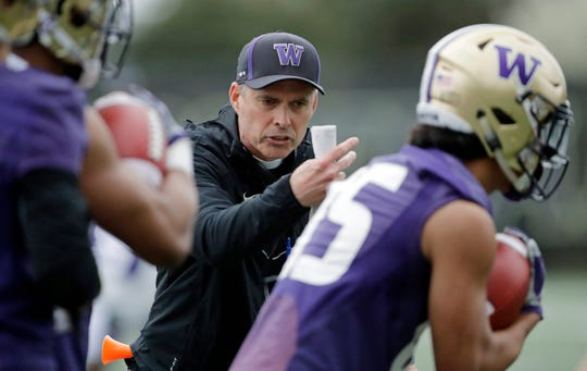 Washington head coach Chris Petersen talks to players as they run drill during the first day of spring NCAA college football practice, Wednesday, April 3, 2019, in Seattle.