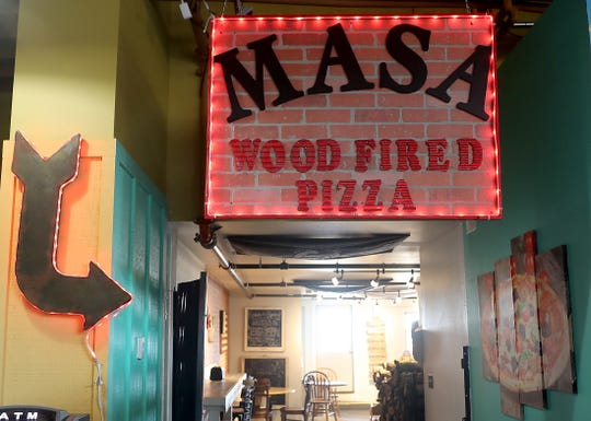 Neon lights point the way to M*A*S*A Pizza located inside the Port Orchard Market. While the founder of the business is being moved out of the area, another family member will keep the business going.