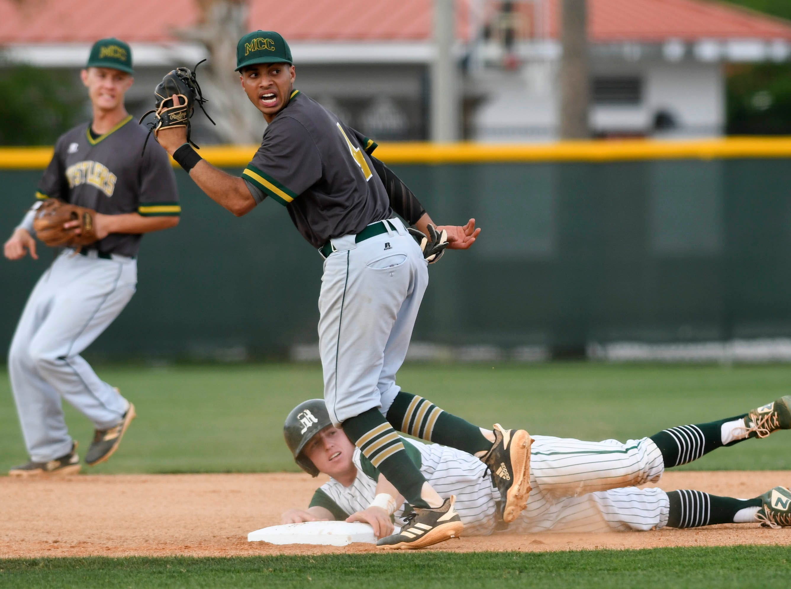 Derick Cantres of Melbourne Central Catholic tags out Melbourne baserunner Jason Blackstone during Wednesday's game in Melbourne.