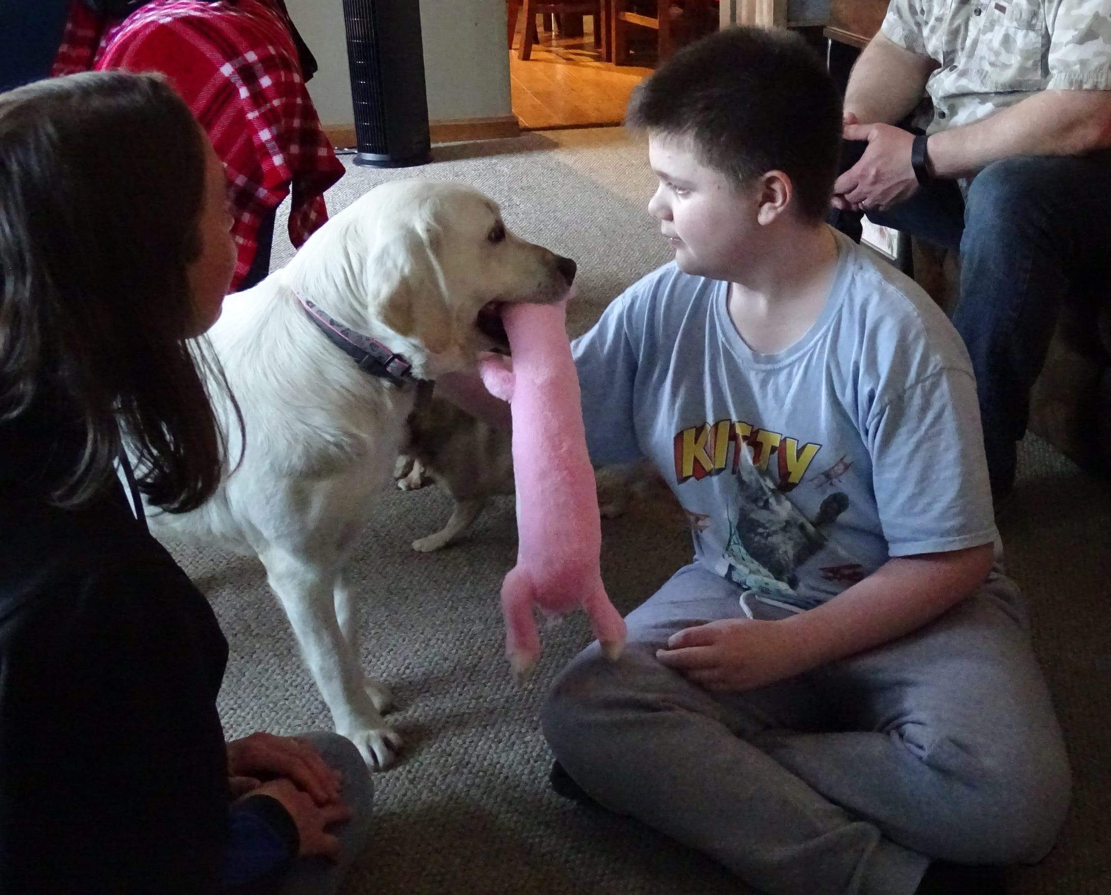 Brenden helps Jewell play with one of her new toys as trainer Erin Gray speaks with the family about the new service dog.