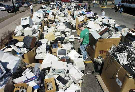 Hunter Hard of Burlington looks through a pile of discarded computers and other electronic equipment dropped off for recycling at Small Dog Electronics in South Burlington on Saturday April 21, 2007.