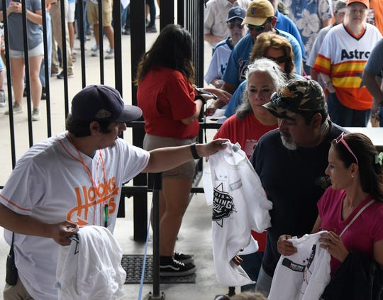 Corpus Christi Hooks fans grab free jerseys at their opening-day game against the Amarillo Sod Poodles on Thursday, April 4, 2019, at Whataburger Field.