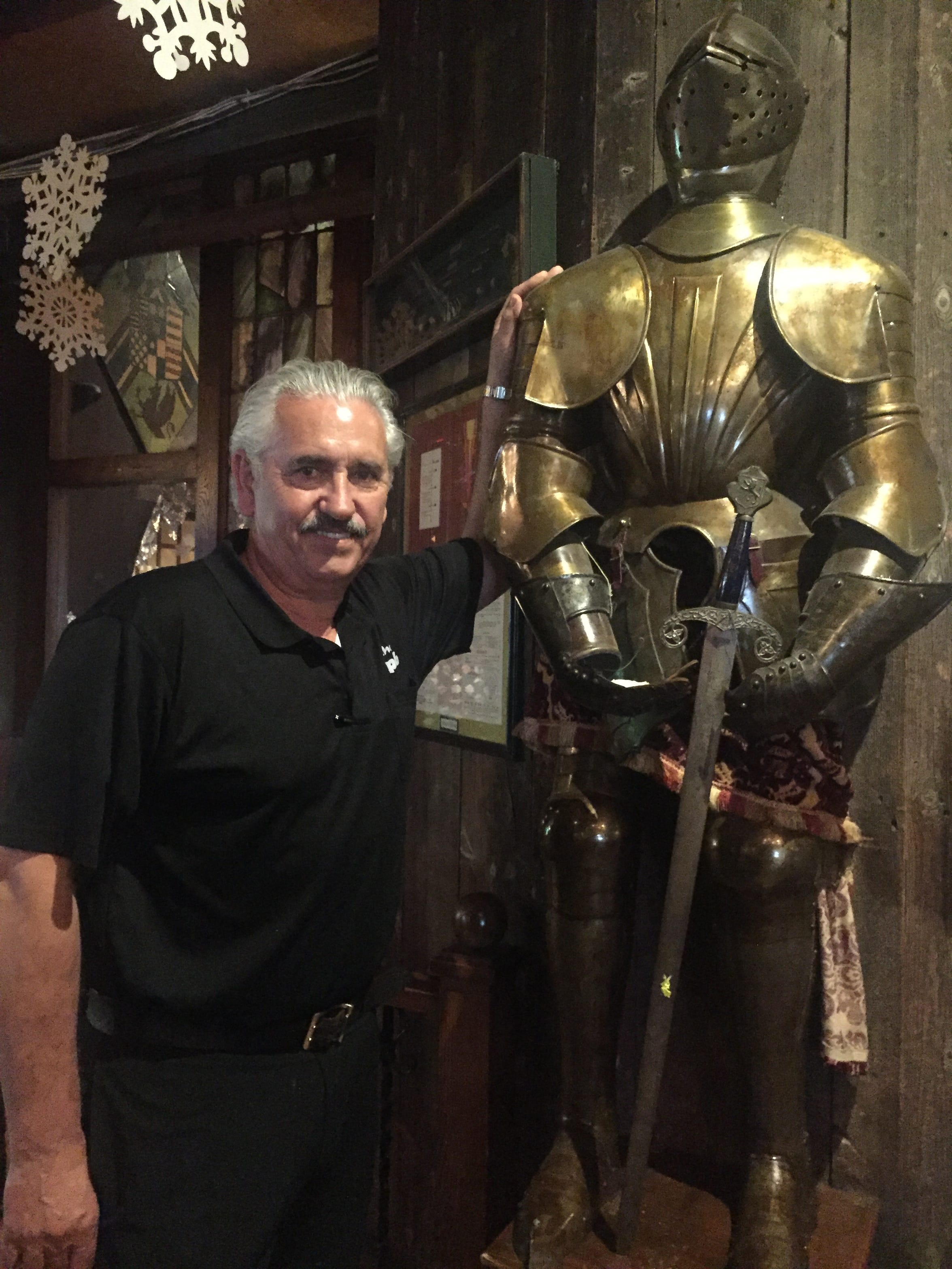 Pub business partner John Laros next to an authentic European suit of armor with sword that has always stood watch inside the Pub in Pennsauken. It is among many antiques in the building