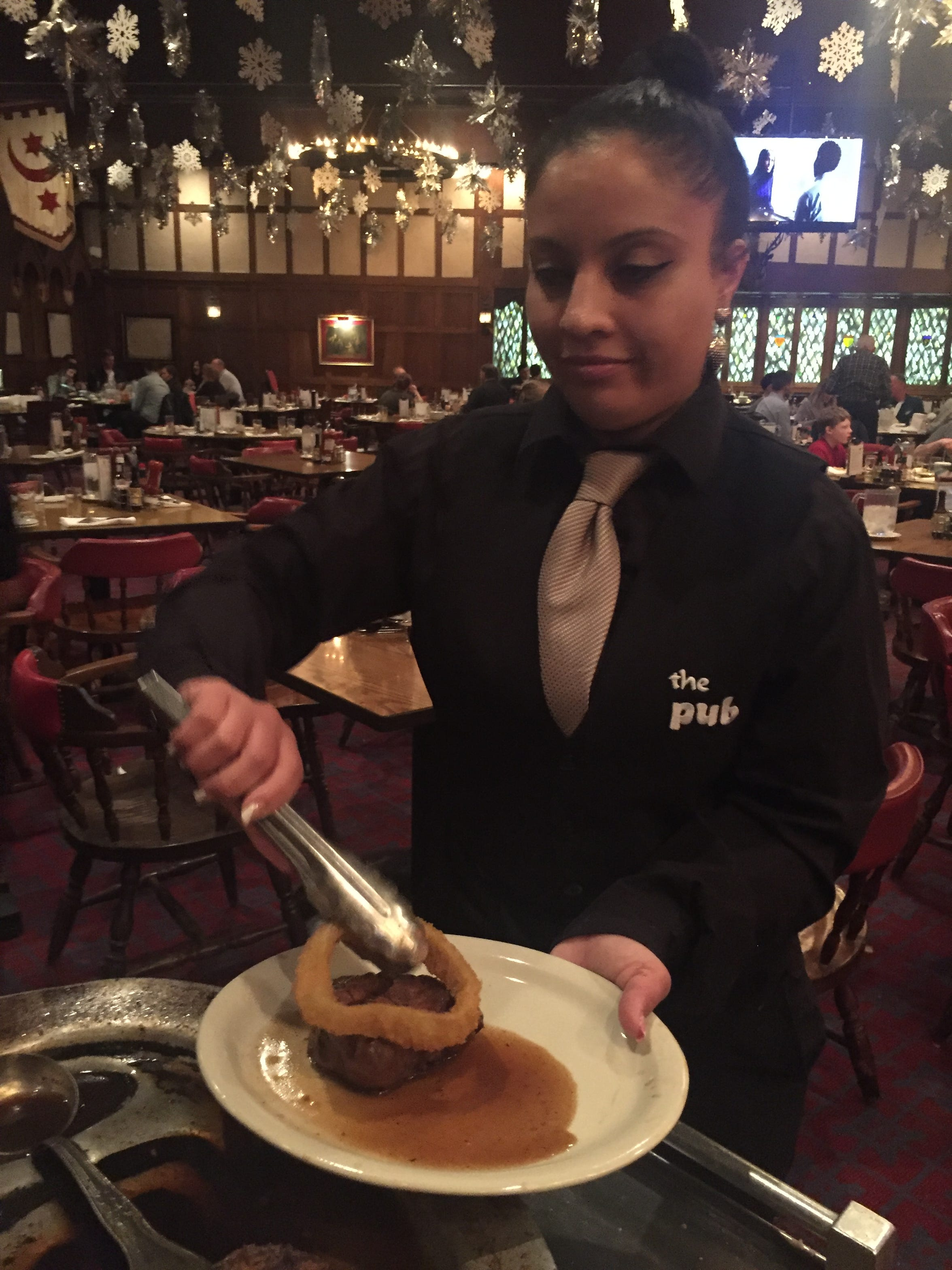 Pub waitress Maddy Alvarado serves a filet at the Pennsauken steakhouse with its signature au jus and gigantic onion ring.