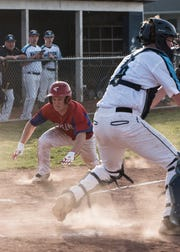 Zane Trace's Cougar Stauffer starts to slide into home to score for Zane Trace during the seventh inning Wednesday night in Frankfort, Ohio. Zane Trace defeated Adena 5-2.