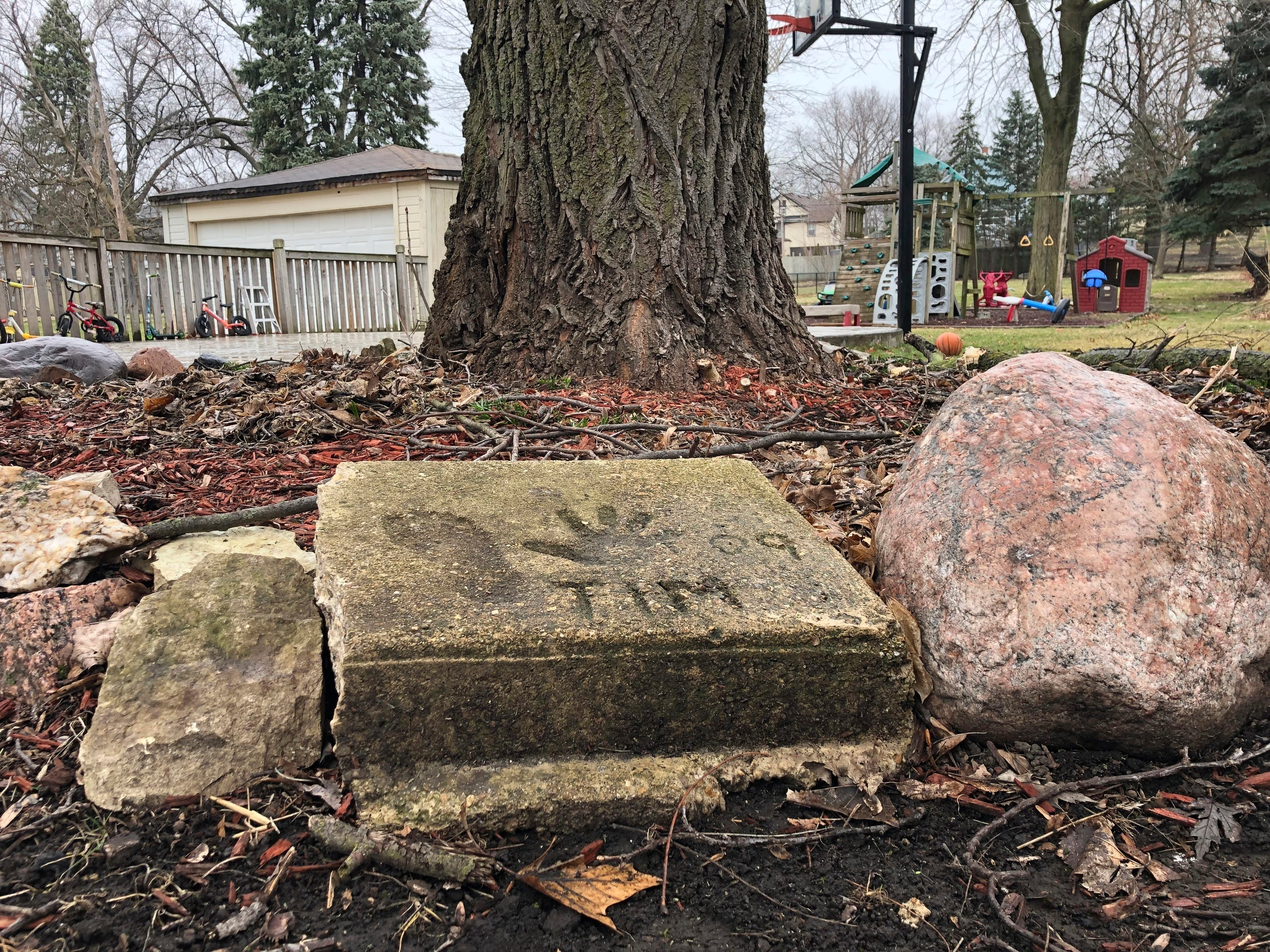 A slab of concrete sits in the backyard of the house where Timmothy Pitzen used to live in Aurora, Illinois. The man who lives in the house now, Pedro Melendez, says he didn't know the boy but saved the concrete slab with Tim's name, handprint and footprint etched in it when he redid the back patio.