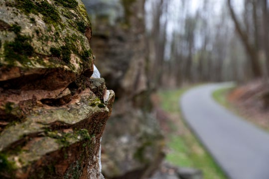 Rock formations jut out of the side of hills flanking the trail at the Clarksville Greenway.