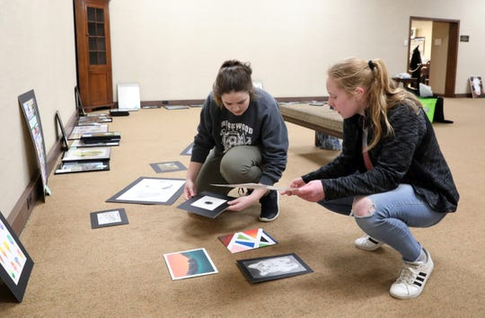Ridgewood High School students Adrianna Flore, left, and Mikenzie Spangler plan out how to hang pieces for the Teenage Talent art show at the Johnson-Humrickhouse Museum in Coshocton.