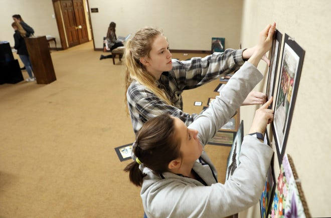 Ridgewood High School  junior Samantha Thompson and Jennifer Bush, executive director, hang a piece for the Teenage Talent art show at the Johnson-Humrickhouse Museum in Coshocton.