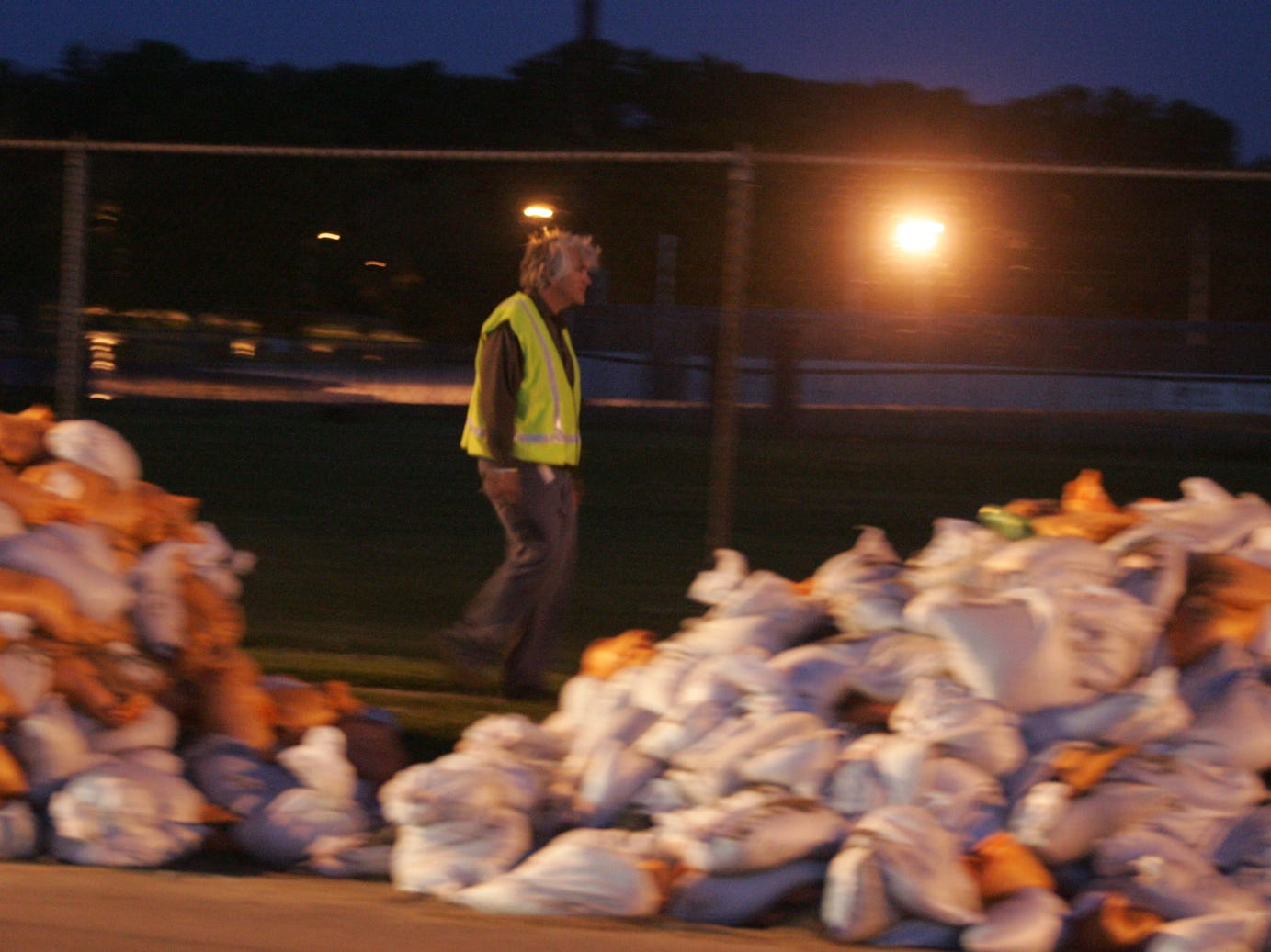 Bill Stowe walks along 2nd Ave. past piles of sandbags at 5 a.m. as work was starting on building a temporary levee during the 2008 flood.