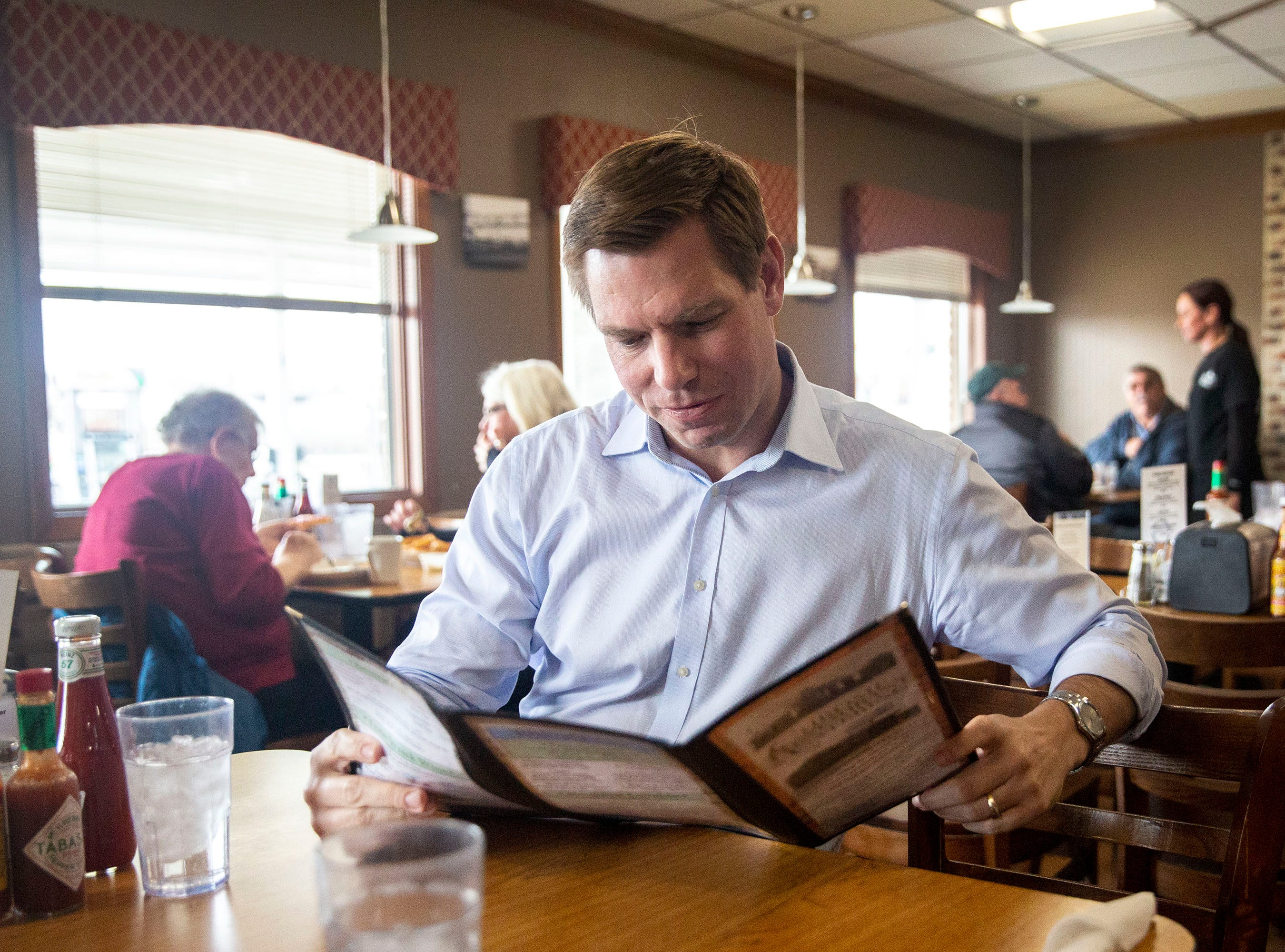 U.S. Rep. Eric Swalwell, D-CA, looks over the menu before ordering a turkey sandwich at Chrome Restaurant and Catering on Monday, April 1, 2019, in Algona. Swalwell was born in Iowa and has made several trips to the state while eyeing a run for president.