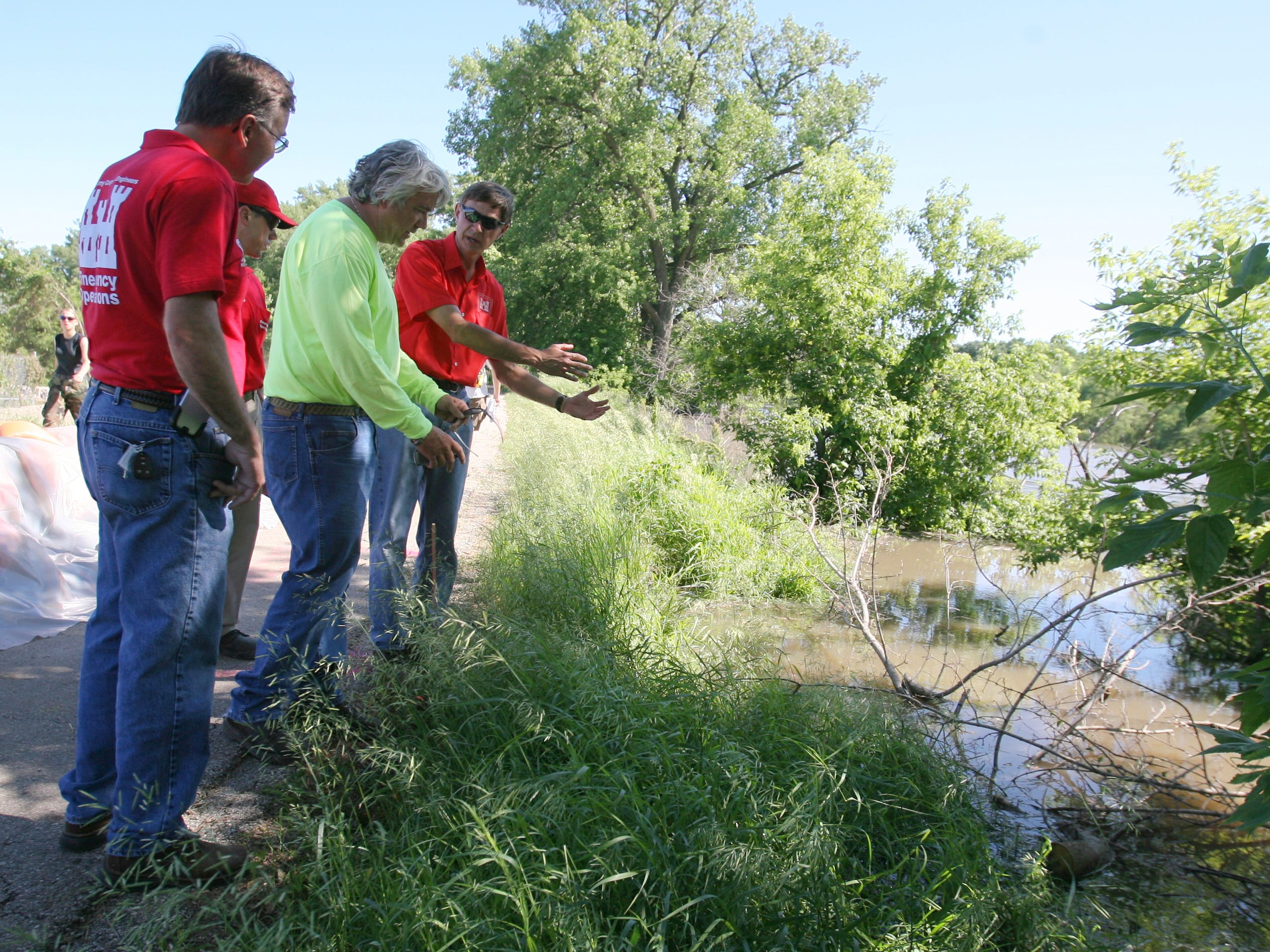 Bill Stowe, in the green, speaks with members of the Army Corp of Engineers about area of soil erosion along the Des Moines River behind North High School during the flood of 2008.
