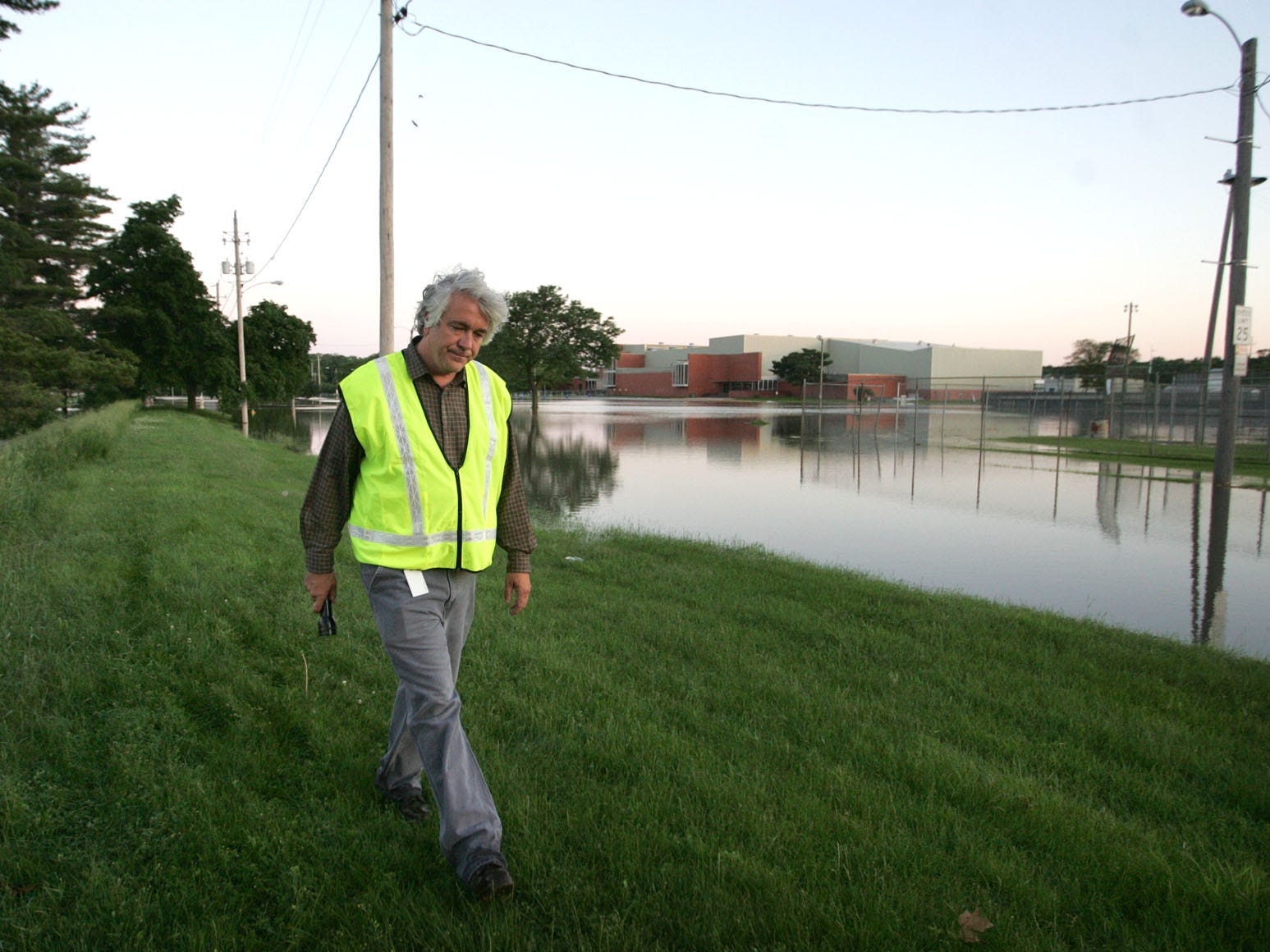 Bill Stowe walks away after viewing the flood waters near North High School during the 2008 flood. A breech in the levee west of North High School brought crews out in droves that morning.