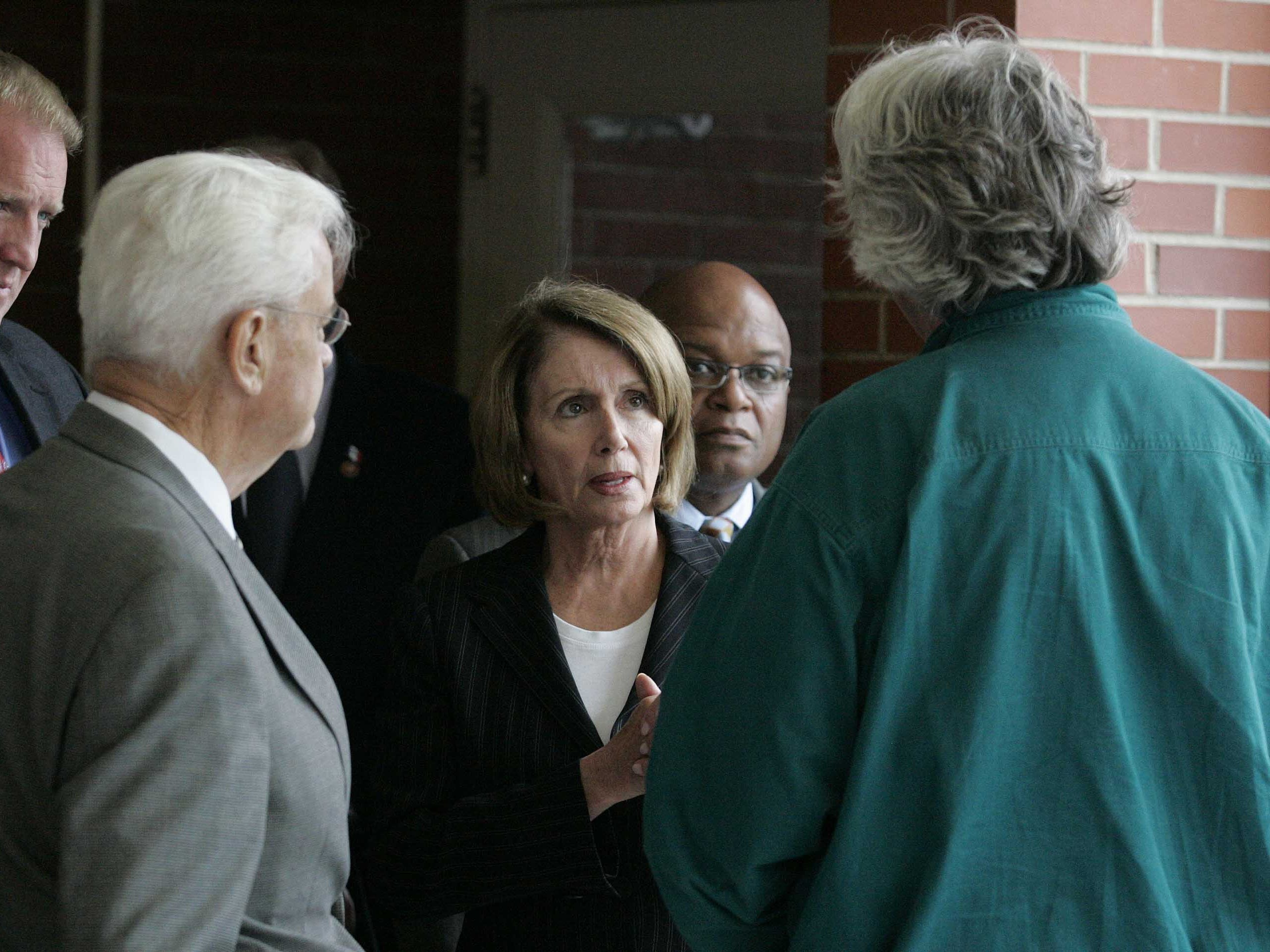 Speaker of the House Nancy Pelosi, center, spoke with Bill Stowe (back to camera) before a press conference at North High School during the flood of 2008. Congressman Leonard Boswell, left, DSM Mayor Frank Cownie, left, Iowa Gov. Chet Culver and North High Principal Dr. Frank Lewis (behind Pelosi) joined him after a briefing on the flood damage to the Birdland Park Neighborhood and North High School.