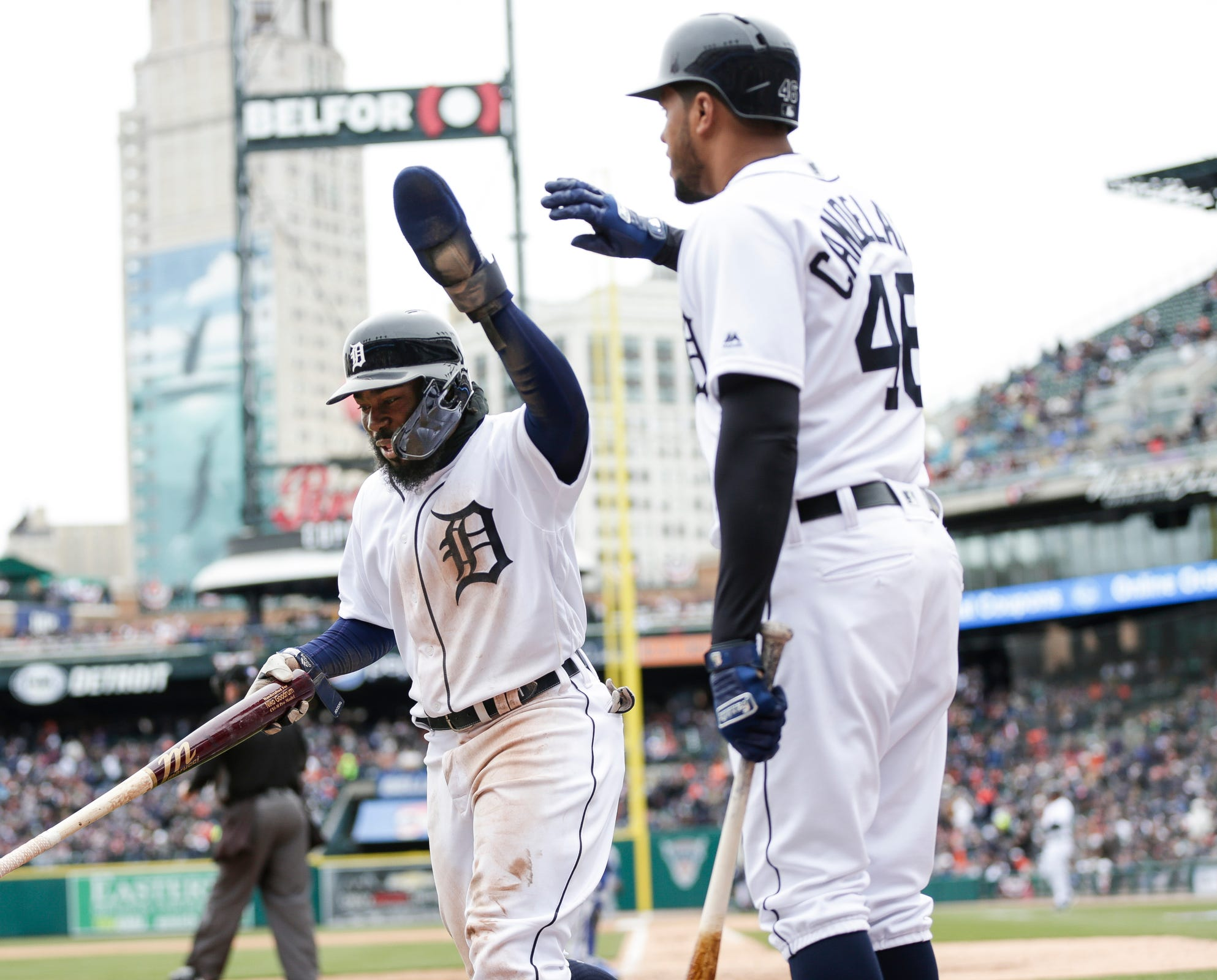 Tigers second baseman Josh Harrison celebrates a run with third baseman Jeimer Candelario during the fifth inning at Comerica Park on Thursday, April 4, 2019.