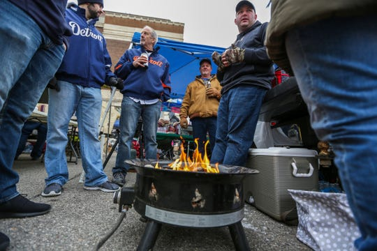 The frigid temperatures kept tailgaters huddles around fires,  during Detroit Tigers' Opening Day at Comerica Park in Detroit on Thursday, April 4, 2019.
