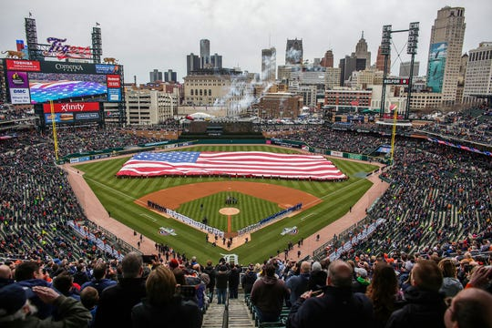 The national anthem is sung as a flag cover the baseball field as fighter jets fly over during Detroit Tigers Opening Day game against the Kansas City Royals at Comerica Park on Thursday, April 4, 2019.