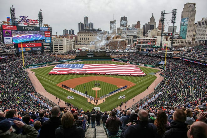 The national anthem is sung by Original Supreme Mary Wilson, as jet fighters fly over and the American flag is displayed, during the Detroit Tigers' Opening Day game against the Kansas City Royals at Comerica Park on Thursday, April 4, 2019.