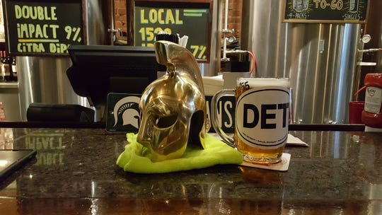 Craig Clemons, 61, of Southfield, sets this brass Spartan helmet on the counter at the Detroit Beer Company  during every MSU basketball game. He lets fans rub it for luck.