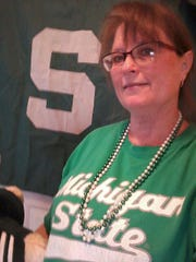 "Amy Daniels Jacoob, who grew up in Grand Blanc and now lives in Indiana, wears the same outfit for every Spartan basketball game for luck: A Michigan State t-shirt, and her ""lucky 2000 championship  beads."""