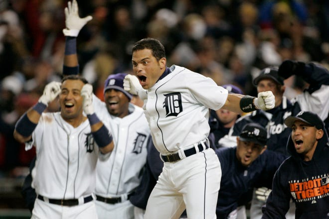 The Tigers' Ivan Rodriguez, center, celebrates with teammates as they wait for Magglio Ordonez to cross the plate after hitting a three-run game-winning home run to beat the Oakland Athletics, 6-3, and clinch the American League pennant in Game 4 of the 2006 ALCS.
