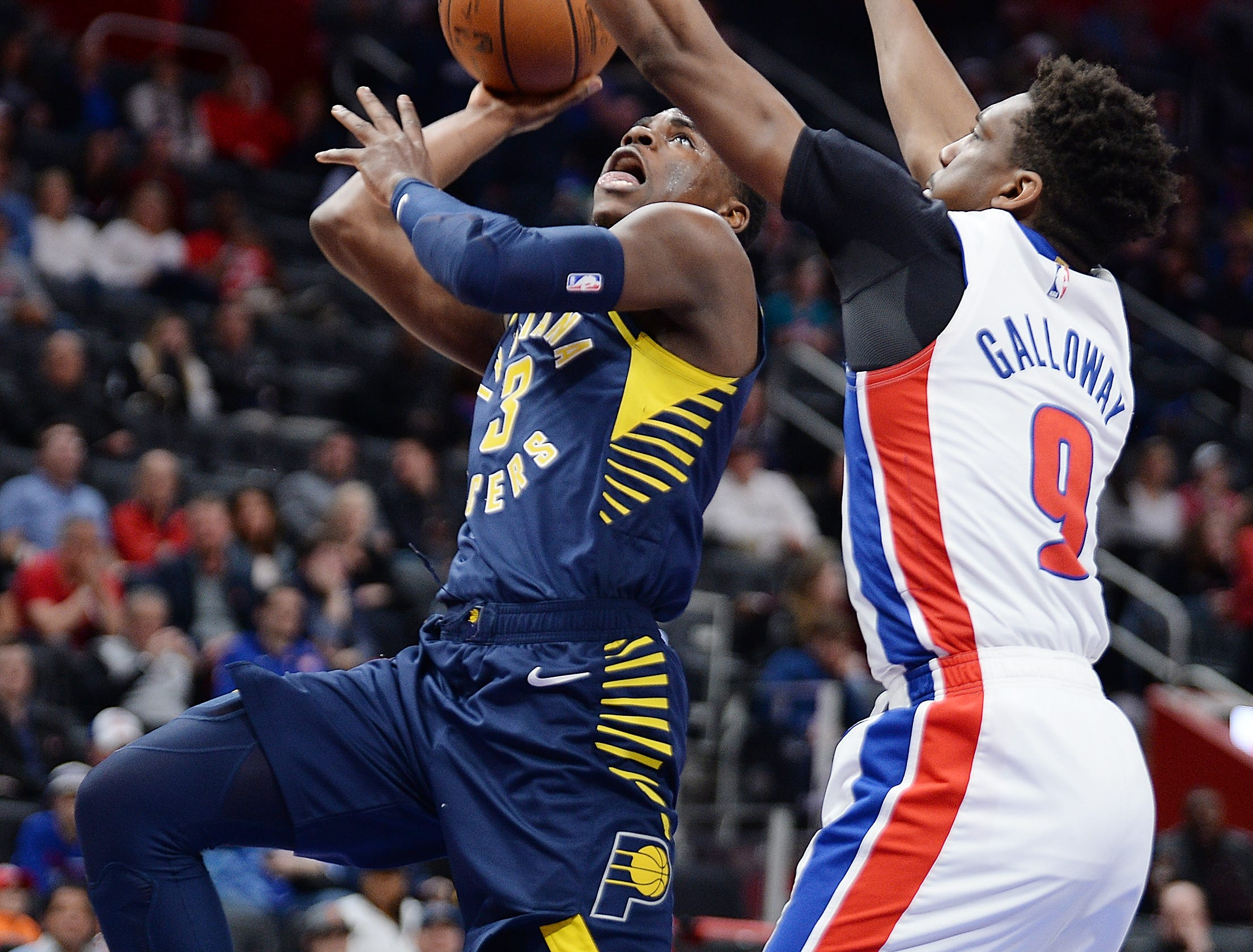 Pacers' Aaron Holiday scores over Pistons' Langston Galloway in the fourth quarter. The Pacers defeated the Pistons 108-89, Wednesday, April 3, 2019 at Little Caesars Arena in Detroit, Michigan.