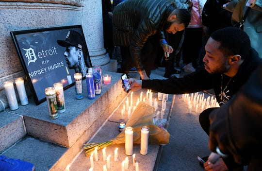 """Fans light candles at a vigil for Nipsey Hussle in Detroit. """"We wanted to bring people together for a hip-hop legend,"""" said promoter Justin Floyd."""